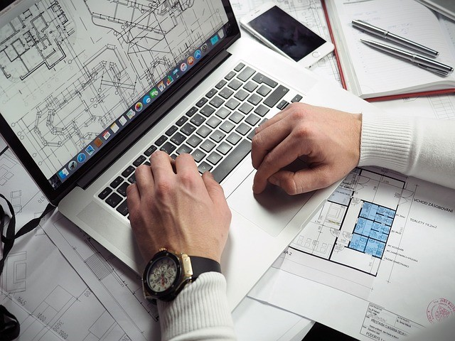 A person looking at building plans on a laptop.
